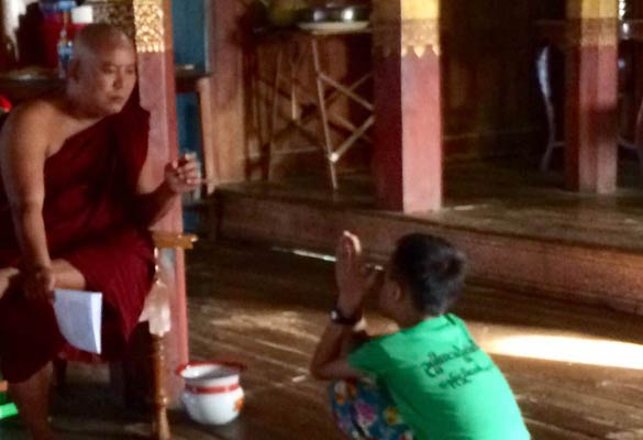 Monge ensina criança a decorar oração
